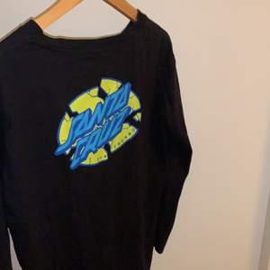 En Santa Cruz tröja. Märket sitter där bak på tröjan och har även tryck på höger armen. Strl 8 och jag är en som är S eller M och den sitter bra på mig.