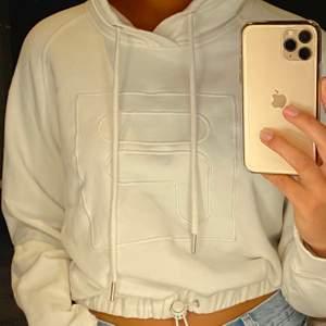Vit, croppad hoodie från fila. Reglerbar resår i midjan. Har luva. Aldrig använd! Rätt så stor i storleken.