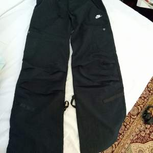 Skitsnygga svarta Nike byxor i storlek 32. Dem är helt oanvända med prislappen kvar. Byxorna är lågmidjade med breda/vida ben och sitter skitfint, men dem var tyvärr för små för mig. Exklusive frakt :)