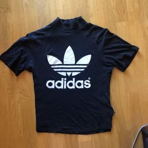 Svart adidas tshirt med turleneck/polo. Annat material på ryggen, nylonaktigt. Frakt 22 kr.