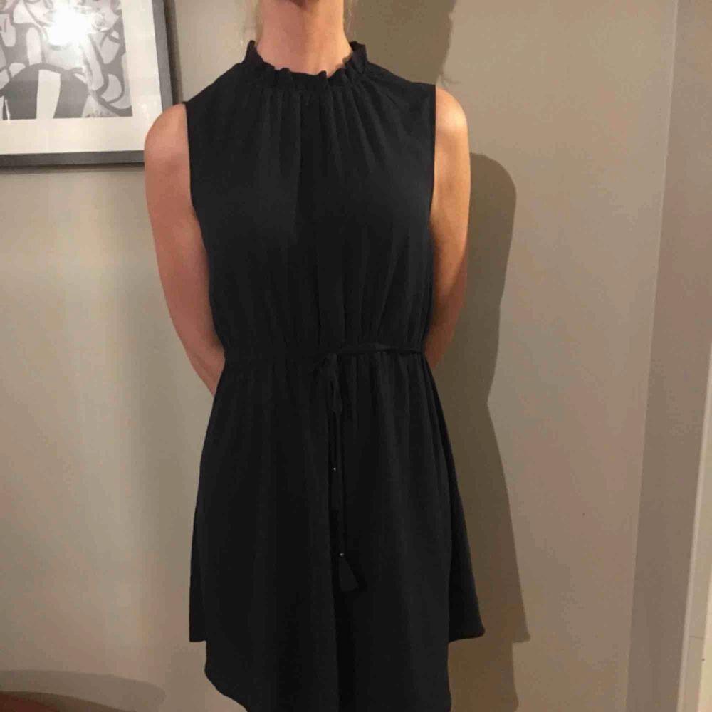 Mörkblå klänning i skirt material med en fin knytning i midjan. Klänningar.