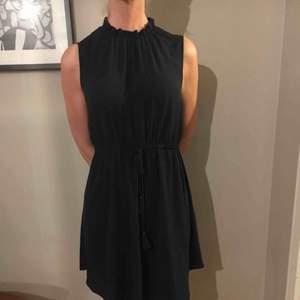 Mörkblå klänning i skirt material med en fin knytning i midjan