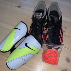 Fotbollsskor som kommer med ett par skydd. Fotbollsskorna är ifrån adidas och är i storlek 37 1/3. Skydden är från Nike i storlek xs. Ett extra snöre följer även med. Dem är använda några gånger men är i nyskick.