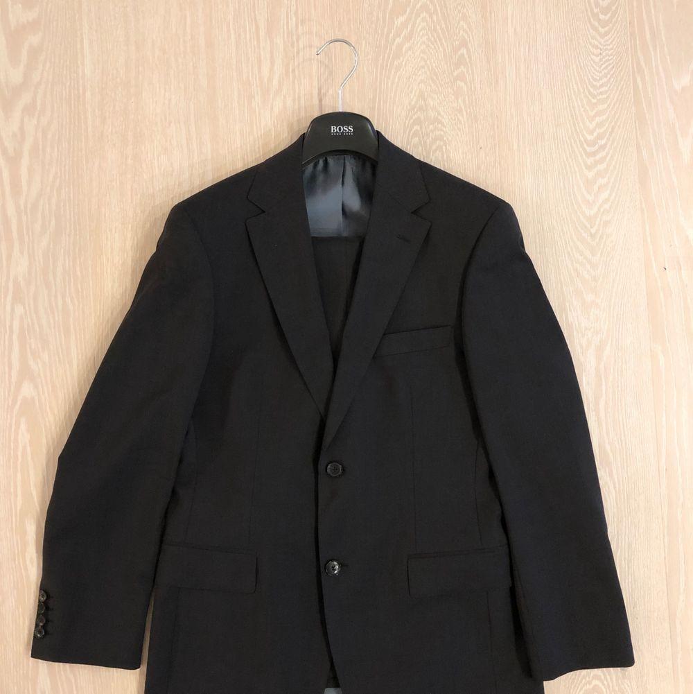 """Hugo Boss kostym i mycket fint skick. Mörkgrå. Högsta kvalitet med tyg från Cerutti. Storlek 46, small, innebär 31"""" storlek i jeans. Kavajen passar även den som har storlek 48 skulle jag säga. Nypris 7000 kr.. Kostymer."""