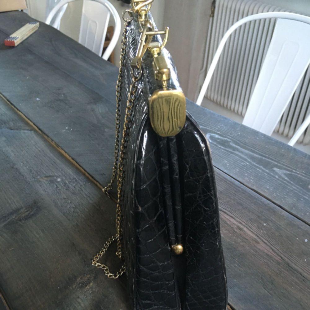 Vintage väska i äkta krokodilskinn.Viss slitage på kanterna på väskan men annars i jätte fint skick. Flärpen syns på bild är trasig men kan lagas.Lås på väskan, nyckel till så man kan låsa.Mått: L30,5 cm H21,5 cm. . Väskor.