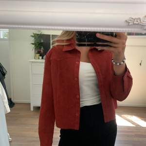 En röd skjorta som är croppad. Supersnygg och skönt material. Kan användas som jacka också.