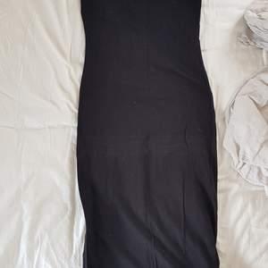 Svart, asymmetrisk, stretchig klänning. Bra skick, lite använd. Normal strl. S.