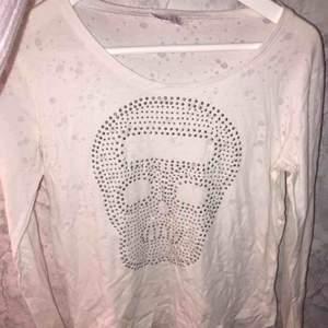 Vit långärmad tröja med döskalle på, det är Storlek 170 så passar bra till S och M skulle jag gissa på!