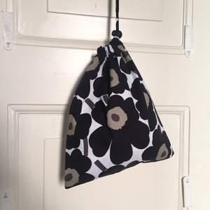 Unik och trendig pouch bag gjord i Marimekko tyget Unikko mini. Går att hänga på axeln eller cross body eller bara hålla i handen. Är också perfekt att ha i en större väska för att hålla koll på grejerna💝