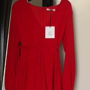 Röd klänning med urringning. Aldrig använd. Längden går till halva låren på mig 170cm lång.