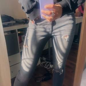 Gråa jeans med slitningar