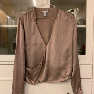 Blus i satin/silkes i lila färg, från Nelly. Jätte fin. Säljer pga för liten i storlek. Det är hål mellan brösten från en säkerhetsnål som suttit där.