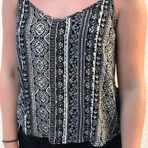Ett luftigt svart & vitt linne med mönster på, två band korsar varandra bak i ryggen (bild 2). Säljer då jag inte använt det på länge