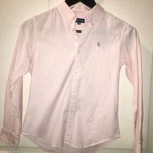 Säljer en Ralph Lauren skjorta i barnstorlek 150, men passar även en XS, dvs 32/34. Frakt ingår. Tar swish! Ljusrosa och vit.