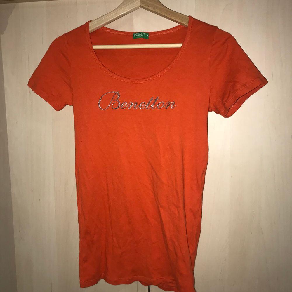 jättefin orange benetton T-shirt köpt second hand. Den har silvrigt tryck på framsidan och är i storlek Xs-S beroende hur man vill den ska sitta. Kan mötas upp eller står köparen för frakten. . T-shirts.