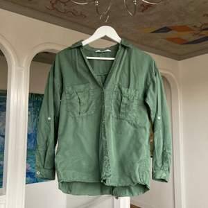 Militärgrön skjorta i skönt material i storlek XS. Lite svårt att fånga färgen på bild men den första bilden stämmer bra överrens! Köparen står för frakt!