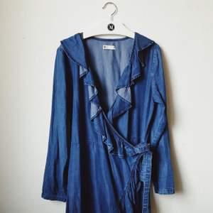 Omlottklänning i denim från Gina Tricot. Endast använd 1-2ggr. Storlek 36 och passar bra till en person med storlek 36-38!
