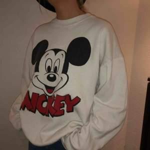 Vit vintage Mickey Mouse sweatshirt med droppade axlar, snygg oversize fit och crewneck. Köpt på blocvintage och är ett original exemplar från disney.