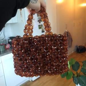 Liten väska gjord av pärlor från H&M med guldig kedja, går att bära på olika sätt! Mått ca 25cm x 20 cm. Frakt tillkommer!