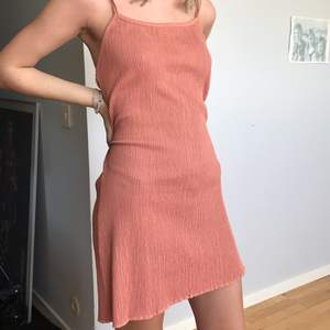 Somrig klänning i peach-aktig färg. Köpt vintage. Passar storlek s-k då materialet är stretchigt.