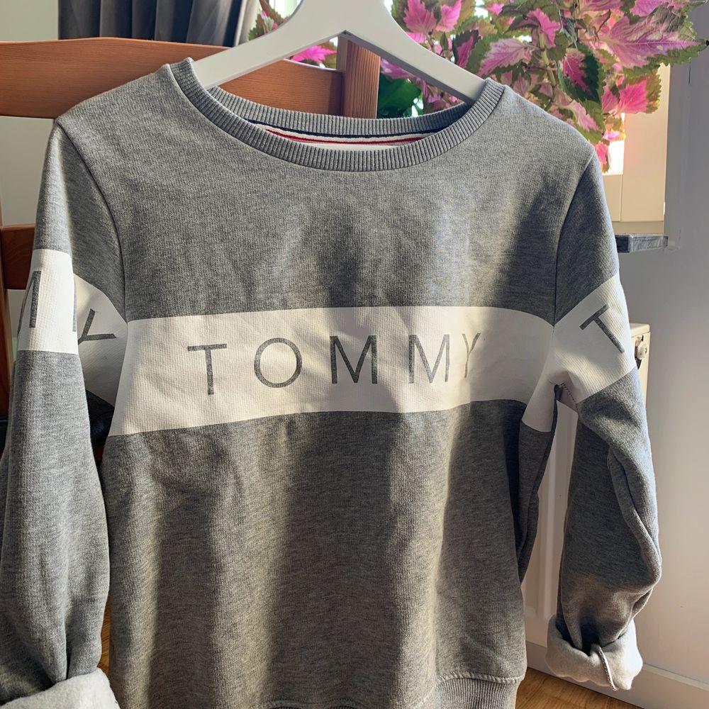 Grå sweatshirt från Tommy Hilfiger med snyggt tryck på både fram- och baksida. Säljer pga att den tyvärr har blivit för liten! Väldigt mysigt material på insida vilket gör den perfekt för höst/vinterväder! NYPRIS: 899kr . Huvtröjor & Träningströjor.