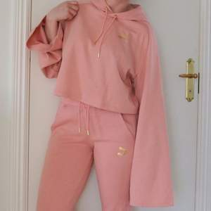 Rosa hoodie/träningströja från Kenzas kollektion med Puma med gulddetaljer. Sparsamt använd och i mycket fint skick. Vida ärmar och är en kort modell. Luftig och skön.