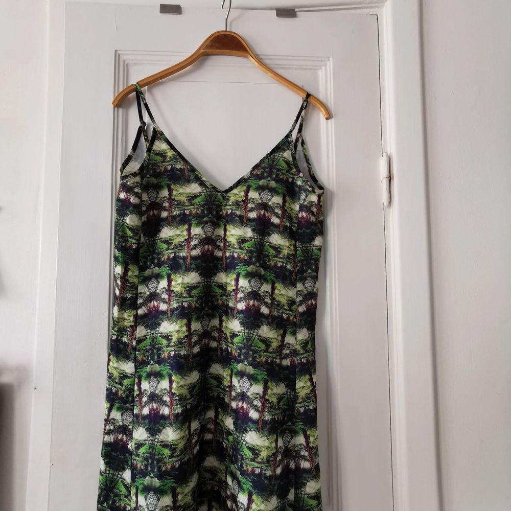 Cool kort klänning med grönt skogsmönster. Lite skejt-aktig modell. Tyvärr lite trasig där bak där ett band som går över ryggen lossnat på ena sidan men väldigt lätt att laga (se bild). . Klänningar.