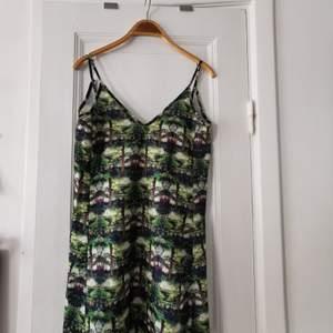 Cool kort klänning med grönt skogsmönster. Lite skejt-aktig modell. Tyvärr lite trasig där bak där ett band som går över ryggen lossnat på ena sidan men väldigt lätt att laga (se bild).