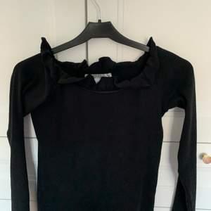 En svart långärmad off shoulder tröja som är ribbad, alltså små ränder på (se bild 3), och har små volanger runt. Storlek 158/164 som är S. Använd 1-2 gånger så den är i bra skick. Säljer för 85 kr + frakt 🖤