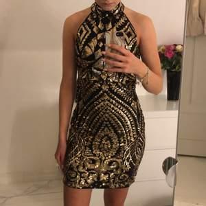 Lite festligare klänning, svart med guldiga paljetter. En liten krage upp på halsen och en dragkedja på ryggen. Sitter tajt, är i storlek 38. Köparen står för frakten!