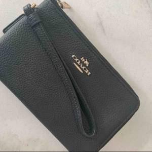 Plånbok från Coach i svart med gulddetaljer för kort, kontanter och telefon (rymmer alla storlekar på iPhone) 2 fack med dradkedjor och en handledsrem