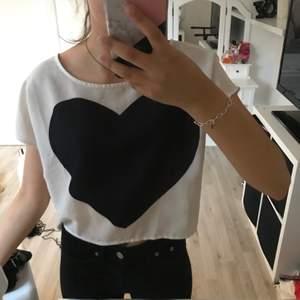 En vit blus med ett svart hjärta och kappar bak, vid ryggen från H&M i storlek 36