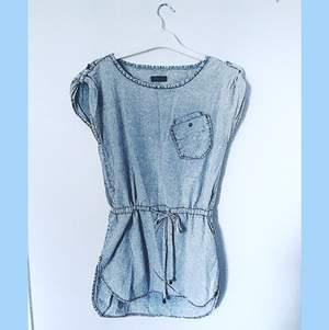 Ljusblå denim(artad) klänning från ONLY i storlek 34. Har en snörning runt midjan att knyta enligt önskad passform, samt en fick på vänster bröst. Ett cirka 20cm långt snitt längst ner på vardera yttre lårben.