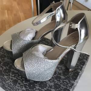 Silvriga klackar från Nly. 14 cm klack och 4 cm platå. Använda en gång. Lite slitna framtill på vänstra skon.