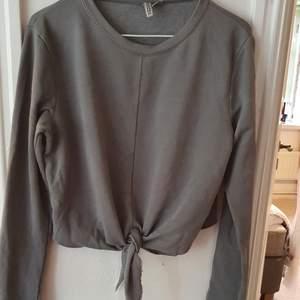 Grå sweatshirt med knytning fram. Även en söm-detalj fram. Köpt för några år sen på H&M men inte särskilt använd. Bra skick! ⭐ Storlek M. Säljs då den inte används. Kontakta vid frågor/intresse 💜 frakt inräknad
