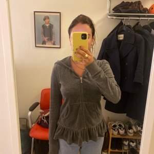 Grå juicy couture hoodie med tryck på ryggen och volang. Nypris ca 1000kr. Storlek XS. 50kr frakt, kan mötas upp i Gbg
