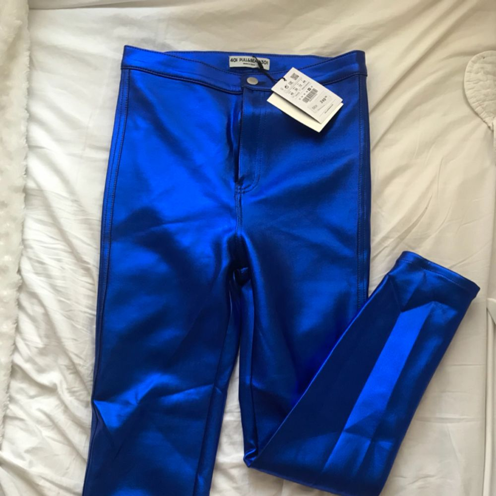 Helt nya blå glansiga byxor från Pull&Bear, lapp kvar. . Jeans & Byxor.