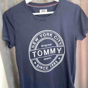 En mörkblå T-shirt med ett vitt tryck på bröstet, den är köpt i somras och aldrig använd. I ett väldigt fint skick och bra kvalité. Nypris-350kr