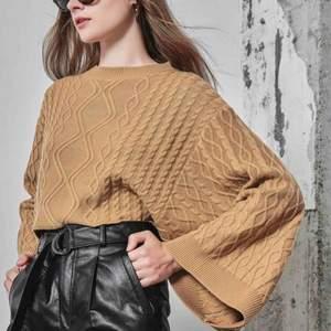 beige tröja från shein med vida ärmar och kabelstickat mönster. helt oanvänd! midjelång. väldigt fin på!