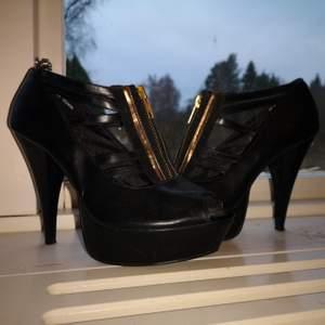 Bekväma och stabila klackar från din sko. Svart fakeläder med dragkedja och detaljer i guld. Platå 3 cm, klack 12 cm. Stl 37.