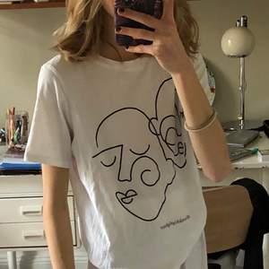 Vit t-shirt med två ansikten ritade i Picasso stil/ abstrakt. Den är från Gina Tricot och välanvänd men i gott skick! ☺️ Köparen står för frakten, jag kan också mötas upp i Stockholm.