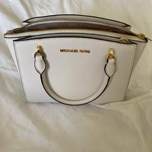 Liten vit axelbandsväska från Michael Kors. En längre rem tillkommer (den som ligger i väskan).