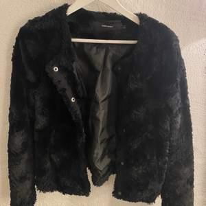 Kort svart fuskpäls jacka med mjukt material och tryckknappsstängning. Använd under en sommar men inget mer. Ordinarie pris: 399,95kr