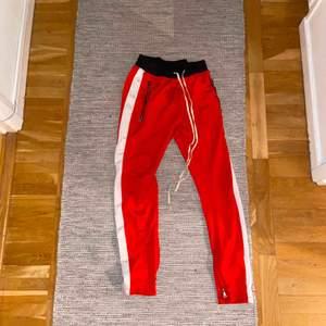Skitfeta röda trackpants i storlek 32, har en slim-fit med dragkedjor längsmed anklarna. Perfekt för en skön och mysig outfit.