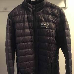 EA7 Emporio Armani dunjacka: Jackan är inköpt på Johnells 2018 för 1800kr, Jackan är i storlek XL men sitter som en L. Den är i väldigt fint skick och knappt använd. Färg: Anthracite gray