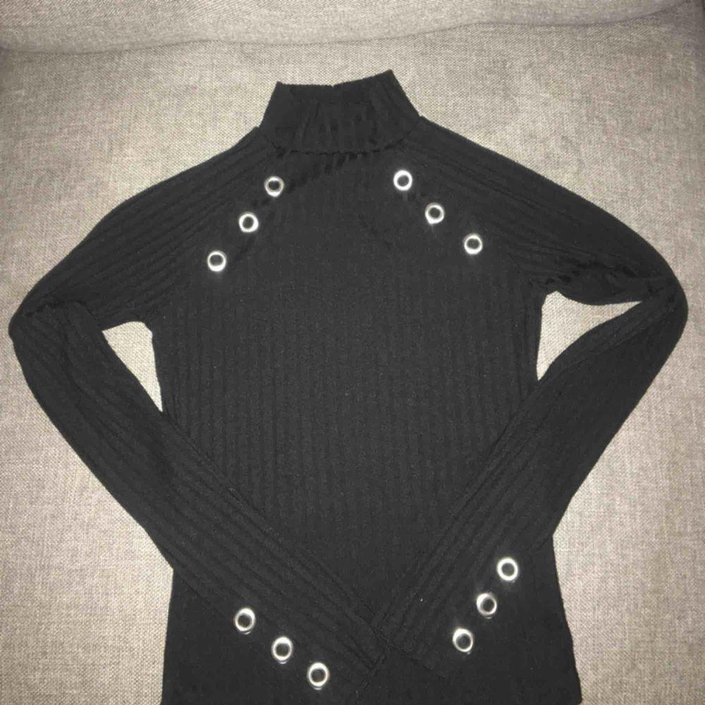 Svart polo tröja med silverdetaljerade hål vid axlar och nederarmar, använd vid flertal tillfällen men fortfarande i fint skick! Köparen betalar för frakt om man ej kan mötas :). Tröjor & Koftor.