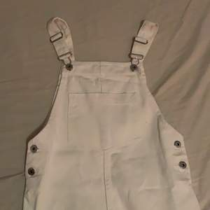 säljer denna jättefina vita hängselklänning i jeansmaterial, från början köpt från HM. snygga knappar på sidorna och ficka på magen, helt oanvänd (lapp kvar)! frakt tillkommer💞