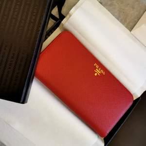 Hel ny och oanvänd plånbok från Prada i den lyxiga färgen röd.  Det är en gåva som aldrig har kommit till användning och endast legat nedpackad i sin kartong.  Inköpt på Prada birger jarlsgatan i Stockholm.  Kvitto, presentkartong, snöre, papper och påse