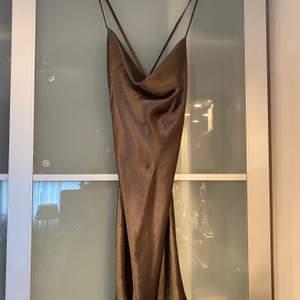 """Grön kort klänning i """"satin"""" från ASOS. Använd fåtal gånger. Knytning i ryggen som går att """"spänna åt"""". Size 42 (mindre i storlek)."""