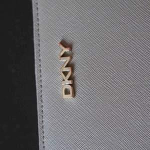 Beige DKNY plånbok. Har ej kvar kvitto, men plånboken är äkta och inköpt i Dubai för antal år sedan. Guldet har börjat tappa sin färg, men är i  399 kr ex frakt eller mötas i Stockholm för 399 kr.  Varan finns på andra köp och sälj sidor 🌟